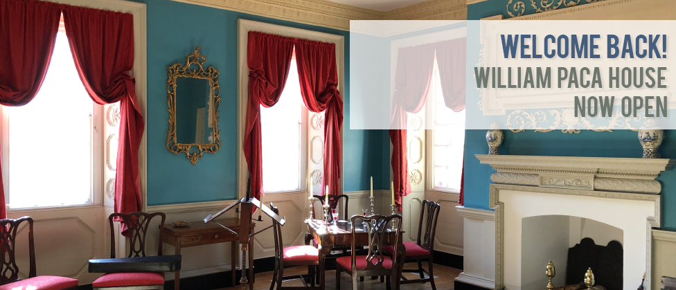 An interior room featuring bright blue walls with off white plaster cornice at the ceiling and a fireplace mantel on the right side of the room. Three windows with red, pulled back curtains to the left of the fireplace, a square table with three chairs and candlesticks, gold gilded frame mirror on the wall, two more chairs, a violin case and a music stand.