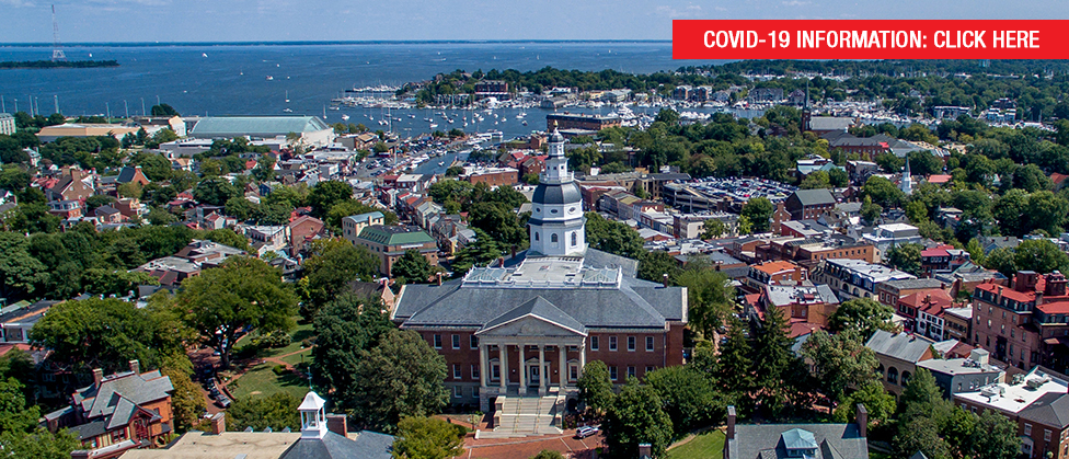 An aerial view of the City of Annapolis with the Maryland State House in the foreground, with buildings, trees, and the waterfront in the background. Text reads COVID-19 Information Click Here